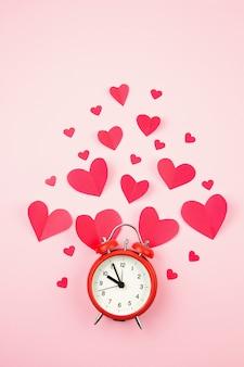 紙の心とピンクのパステル調の背景の上の目覚まし時計。