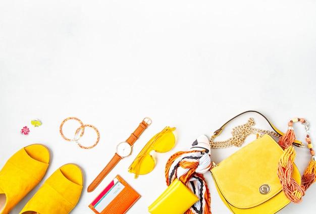 フラットは黄色の色で女性のファッションアクセサリーを置きます。