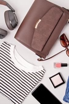 女性のファッションアクセサリー、サングラス、イヤホン、ハンドバッグ。