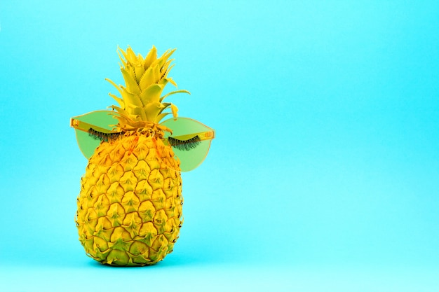 人工まつげとサングラスの黄色い塗装パイナップル
