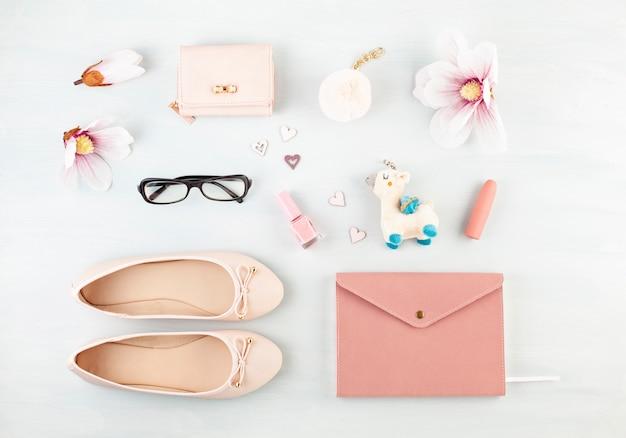 ピンクのパステルトーンの女の子春夏アクセサリーとフラットを置きます。カジュアルな都会的な夏のスタイル