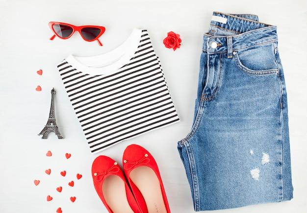 Модная плоская планировка с французским стилем женского городского наряда с футболкой, балетками, солнцезащитными очками и джинсами.