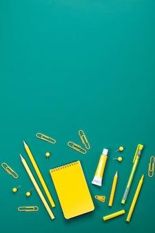黄色い学校は緑の板の上に供給します。教育、勉強、そして学校に戻るコンセプト