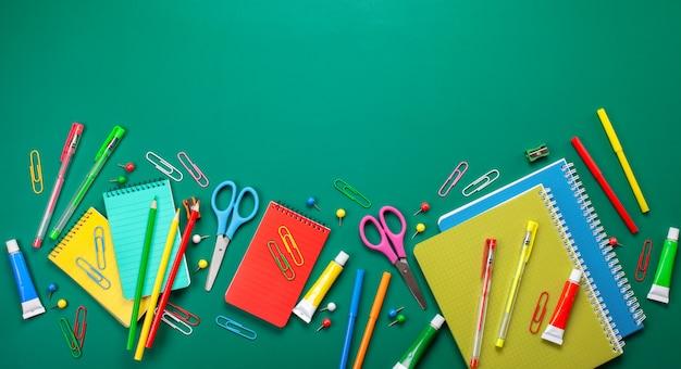 グリーンボード上のカラフルな文房具と学校のコンセプトに戻る
