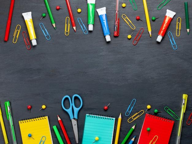 黒板の上のカラフルな文房具と学校概念に戻る