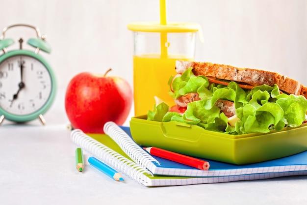 プラスチック製のお弁当箱でヘルシーなランチに新鮮なサンドイッチとリンゴ