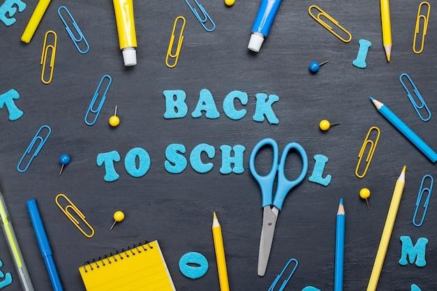 黒板の上にカラフルな文房具で学校のテキストに戻る
