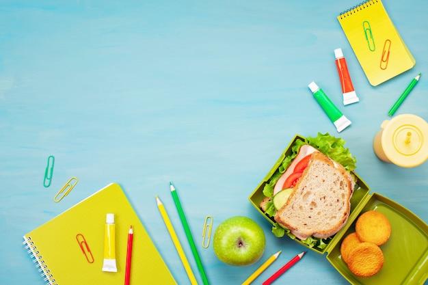 Свежий бутерброд и яблоко для здорового обеда в пластиковой коробке