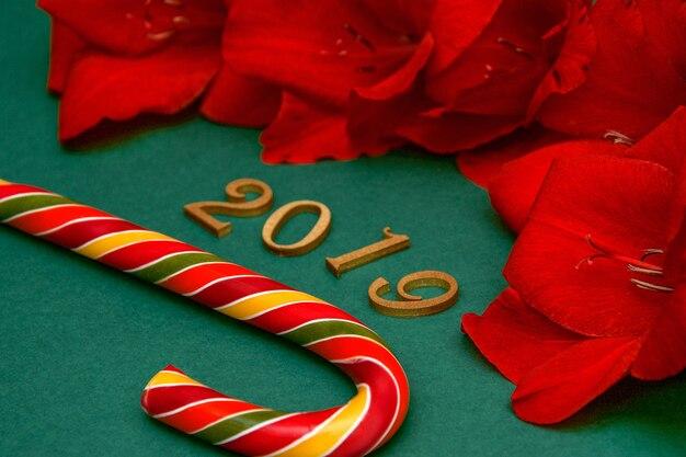 クリスマスの赤い花と緑の背景に新年のカラフルなロリポップ