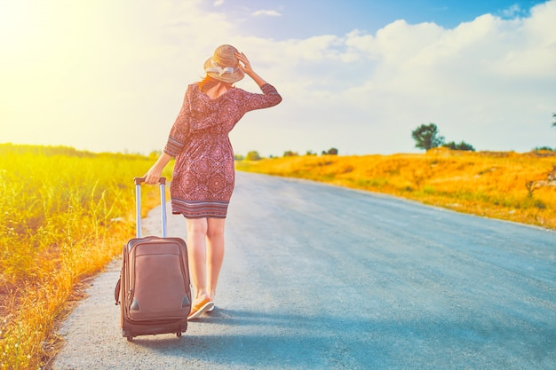 スーツケースと女性のヒッチハイカー