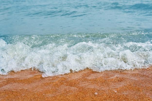 Песчаный пляж с волнами от моря.
