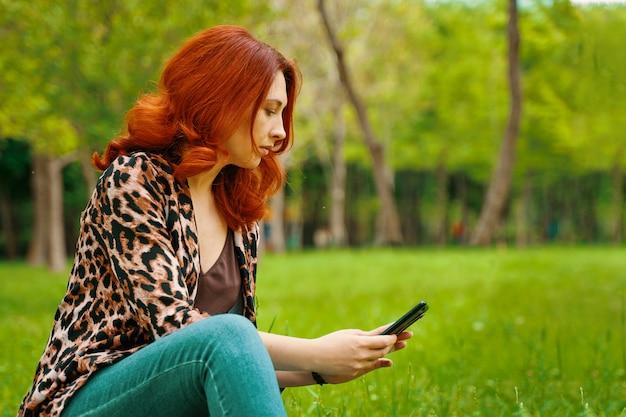 女性は彼女の携帯電話でメッセージを入力しています