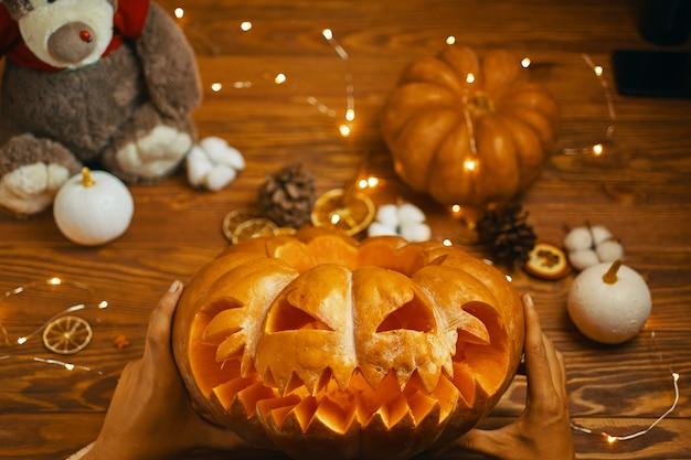 伝統的な秋の休日ハロウィーンのジャックのランタンオレンジカボチャを探している男性。