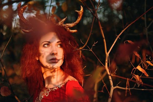 Женщина в длинном красном платье с рогами оленя в осеннем лесу