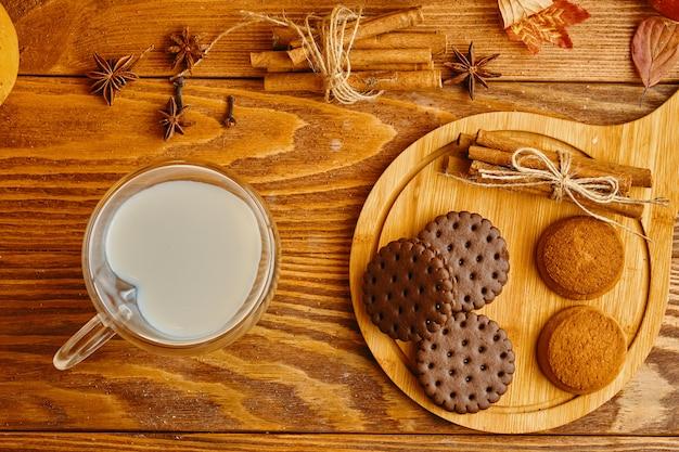 テーブルの上の牛乳とクッキー。クッキーのスタックと木製のテーブルとシナモンのミルクのガラス。