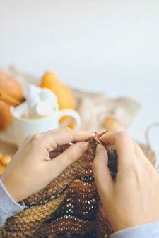 Женщина вяжет шерстяную одежду. одна девушка пьет горячий шоколад с зефиром. карантин