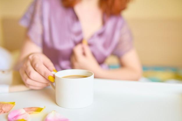 朝早くベッドでコーヒーを飲む紫色のシルクローブのかわいらしい女性。
