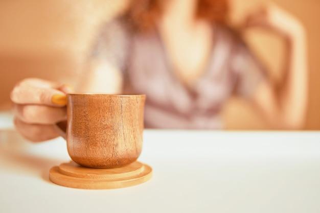 ベッドとカップで朝早くコーヒーを飲む紫色のシルクローブのビーティーな女性