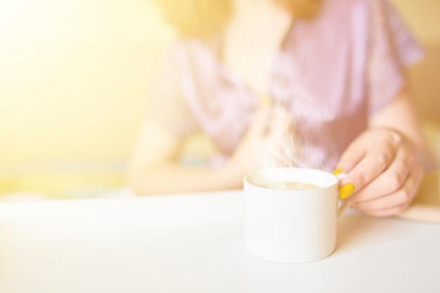 ベッドで朝早くコーヒーを飲む紫色のシルクの服で優しい女性