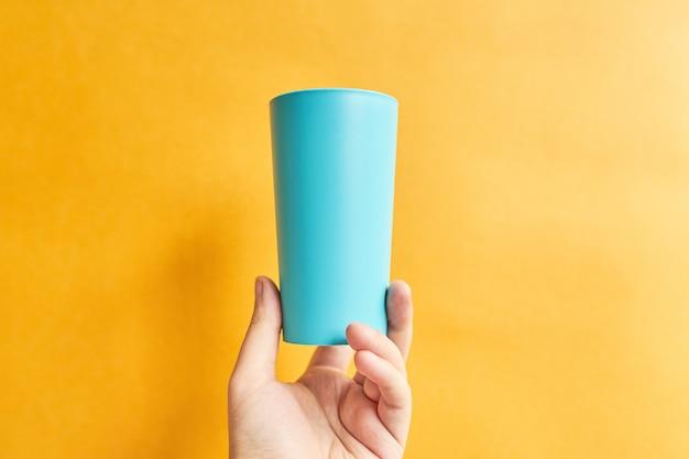 黄色の背景に手にブルーカップ。