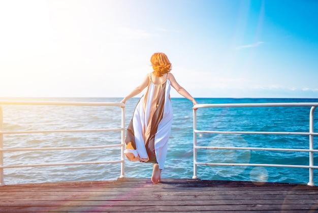女性は手すりの桟橋の海の美しい景色を賞賛します。