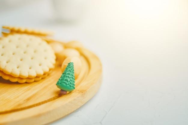 お祝いの夜にテーブルにクッキーとミニチュアクリスマスツリー