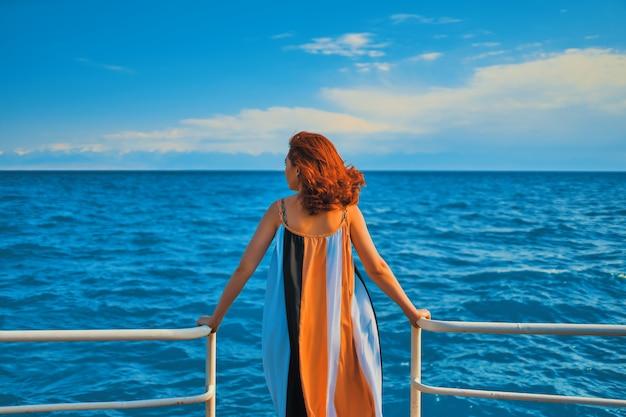 桟橋の女の子の後ろに。桟橋に立っているカラフルなドレスの女性。