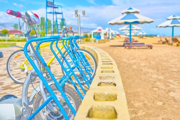Стоянки для велосипедов с велосипедами на берегу океана на фоне пляжных зонтов