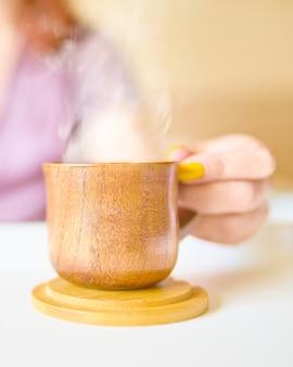 朝早くベッドでコーヒーを飲んで紫色の絹のローブでかわいい女
