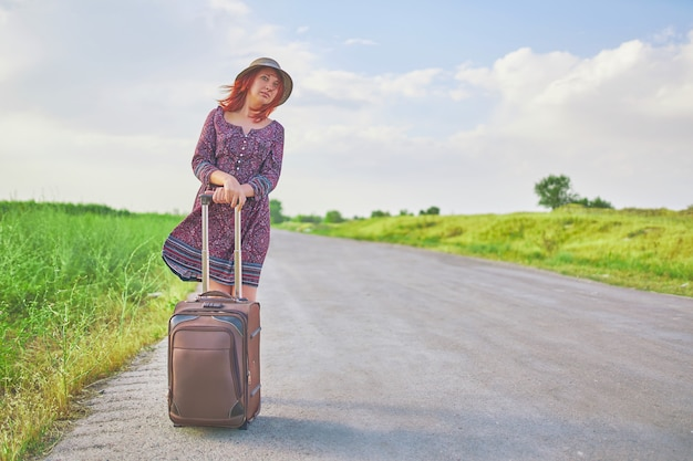 夏のドレスと帽子春の道でスーツケースとヒッチハイクの女性旅行者。