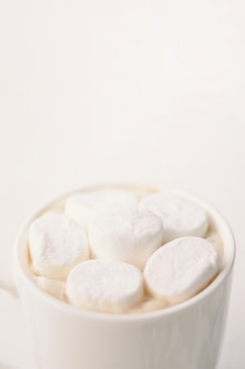 テーブルの上の白いマグカップでマシュマロとホットコーヒー。垂直クロップ