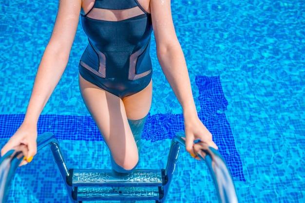 プールで泳いでいる女性。青い水プールで泳ぐ水着を持つ女性。