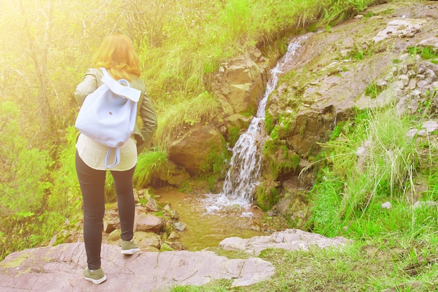 山の森を歩く女性ハイカー。