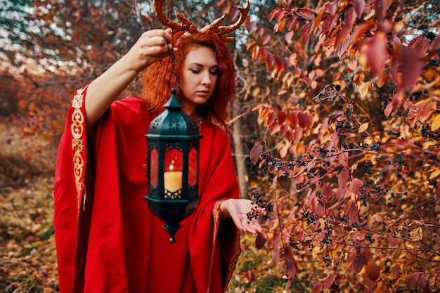 秋の森の鹿の角を持つ長い赤いドレスの女性。