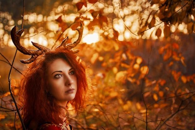 Женщина в длинном красном платье с рогами оленя в осеннем лесу.
