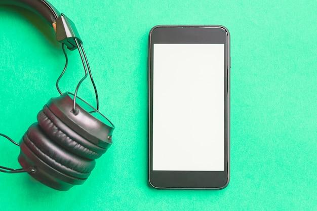 ヘッドフォンとカラフルな背景のスマートフォン。