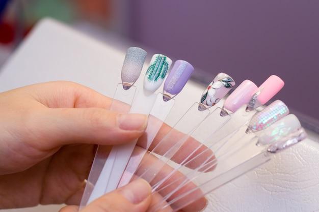 女性は色の異なる色の付いたテストネイルポリッシュを握り、絵画のための色を選びます