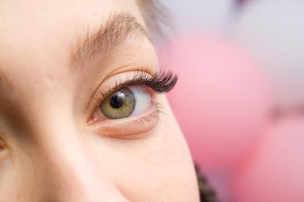 まつげエクステの手順。長いつけまつげを持つ女性の目。
