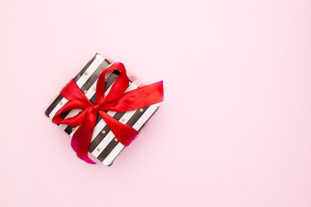ピンクのテーブルトップビューで分離された赤いリボン弓と白と黒のストライプのギフトまたはプレゼントボックス。