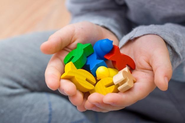 子供のレジャーの概念の手にボードゲームの多色の木のチップの魚の数字