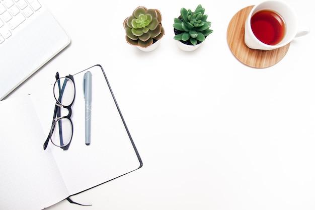 Рабочая область с ноутбуком, блокнотом, альбомом для рисования, сочными, чашкой чая