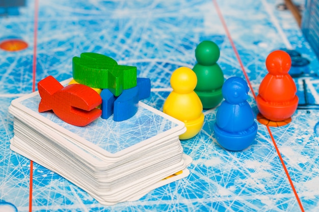 ボードゲームとキッズレジャーのコンセプト - 赤、黄、青、緑の木のチップフィギュアとプレイ
