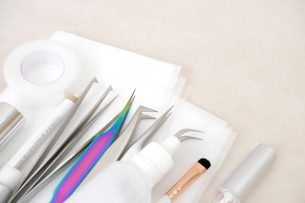 Процедура наращивания ресниц. инструменты. клей, пинцет, кисти. салон красоты, мода и женщина составляют концепцию