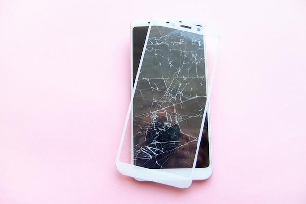 壊れたグラスタッチスクリーンが分離されたモバイルスマートフォン。サービス、修理、技術そしてミニマリズムの概念。