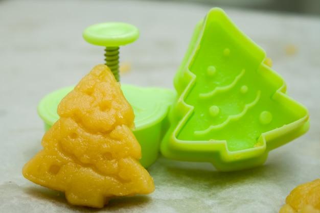 生の生地とフォームの子供のためのクリスマスクッキーの準備