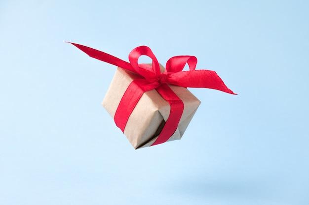 Подарочная коробка с красной лентой на синем фоне.