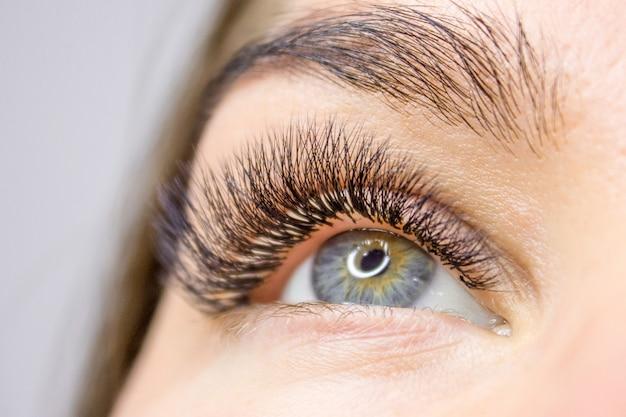 まつげエクステンション手順。長いつけまつげの女性の目。美容とファッション