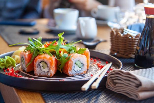 Суши-ролл японская еда в ресторане. калифорния суши ролл с лососем, овощами