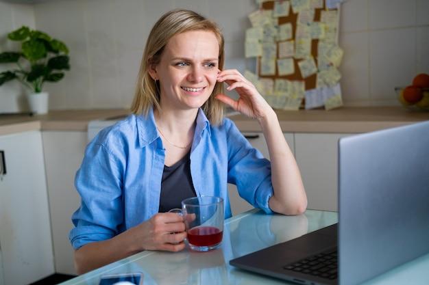 Счастливая женщина, использующая ноутбук для видеозвонков друзьям и родителям, улыбающаяся девушка сидит дома на кухне