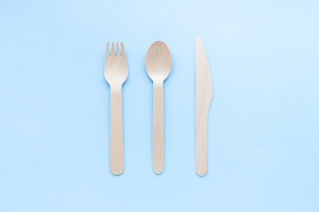 Экологически чистые одноразовые кухонные принадлежности на синем фоне. деревянные вилки и ложки. экология, концепция нулевых отходов. вид сверху. плоская планировка